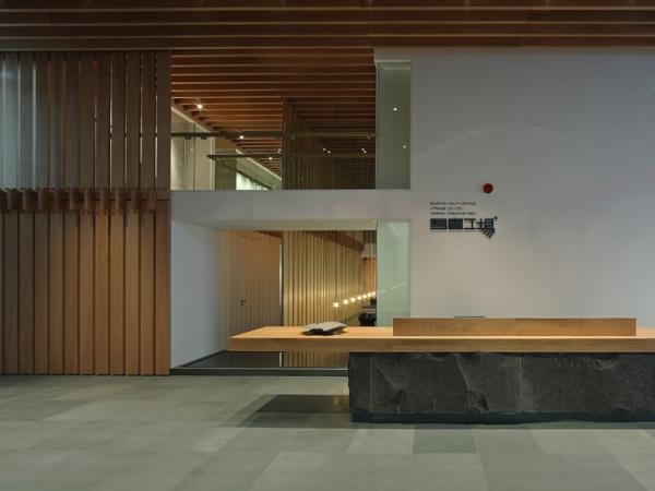 办公室前厅设计效果图,办公总部选在大厦的顶层既拥有了良好的视野,同时让设计工作更加贴合市场,以便把握流行的趋势、激励不断创新。然而市场的繁忙和喧嚣却与办公空间所需要的安静、有序的本质要求相悖。接待大厅右侧一面白墙镶嵌着长窗与左边顶天立地的木隔板如一幅展开的画卷。木质案台(接待台)挑空悬置与大青石之上,与室内的青砖铺地相互映衬,顶部齐齐阵列的木格栅、案台左侧若隐若现的灯光和水-上下左右、前后远近各种空间界面的虚实转换;淡雅的色彩和熟悉的材质,顶面的木格栅似瓦屋脊梁的氛围让人多了些许亲切。  办公室前厅设计效