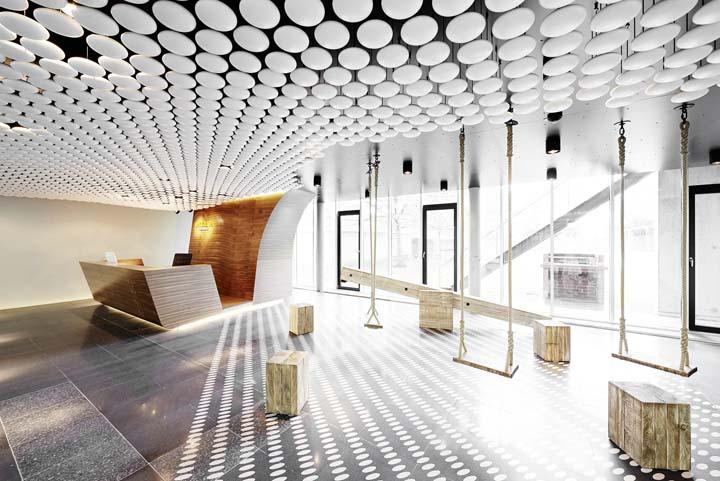 办公室顶面白色棋子波点造型,活力、动感是办公室设计的两大关键词。当人们一进入开敞的接待大厅就能感受到设计团队的氛围营造。圆润的白色围棋子般波点造型带来惊艳的视觉效果;大厅一角的木质秋千充满了童真乐趣。新颖而独特的设计元素将人们一路引领至工作区。 特别是白的围棋造型的N个旗子拼凑的造型很是壮观而且也很有新意。  办公室顶面白色棋子波点造型  办公室顶面白色棋子波点造型