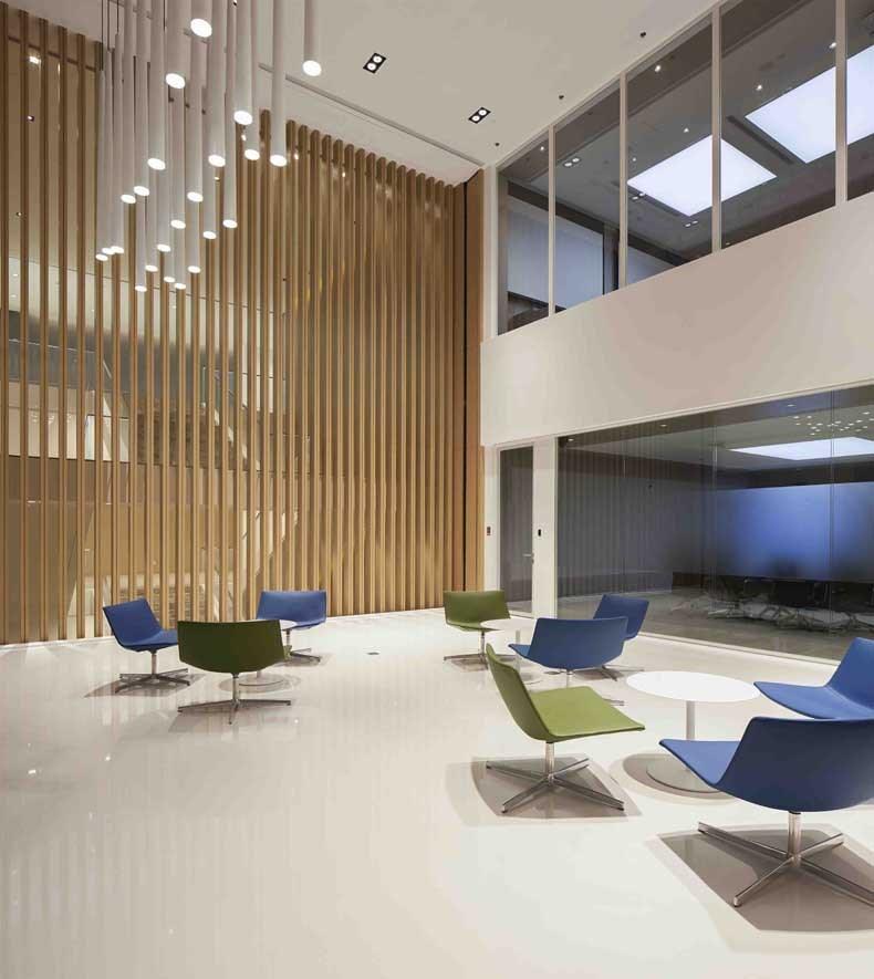 作為印尼金融工業巨頭的金光集團,位于上海的亞洲新總部辦公室,主要空間近9000平米由2層半辦公空間組成,南北兩側及中部分別開辟了近500平米的3個挑空層,使空間組合靈動,布局張弛有度,視覺開闊明亮。  作為主要接待區的南側挑空層,層高8米的垂直木色格柵LOGO墻壁配合兩側白色折紙造型的GRG裝飾板,以及極簡純平的白色接待臺,分別象征了造紙行業的木原料,半成品紙漿及成品紙張這一行業特征,巧妙融入到空間設計元素里。對應北側的挑空層開辟了員工閱讀中心,為員工提供了溫馨舒適的休閑空間,作為整個辦公中心的過渡空間避免了過于縝密的辦公空間壓迫感。 員工辦公區選擇了橙,綠,藍色作為的點綴色,給予了APP集團一個活力,健康并專業的辦公室愿景。