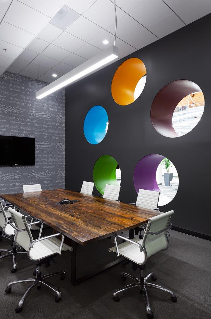 """整体色调由Ooyala的标志色为主导,深浅不一的灰调中,跃动的靓丽色彩带来清新活力的时尚氛围。开敞的空间、多元的功能、奔放自由的设计令创意灵感由此迸发。 文字由时尚办公网编译,转载请注明。工程部门与营销部门之间的协作室,设置了一道移动隔墙,可以根据工作需求改变空间布局。功能布局还包括圆形会议室、有移动隔墙的培训室、休闲咖啡区、图书室、健身游戏室、以及为所有员工准备的大型午餐休息区等,这些功能区由一条宽敞的水泥过道连接起来。这条水泥过道的设计可是大有深意哦,年轻好动的人们可以踩着滑板在这里风风火火自由畅行;当然这里也可以作聊天步道、或者漫步思考。裸露的顶面、抛光的水泥地面、只在需要静音的地方铺以地毯。从入口大厅既能感受到柔软的""""摇篮""""设计主题,轻盈的球形灯具与公司logo相呼应;两个圆形的空间造型象征幼虫成长的温暖茧壳;一个长约25英尺如隧道般的创意空间,呈现出有趣的空间透视效果,其灵感源于相机变焦镜头的成像;休闲背景墙上的彩色圆孔造型,不仅可以随意小坐,也令空间顿增许多可爱童趣。Ooyala是全球电信和IT服务公司澳洲电讯(Telstra)旗下的美国子公司,是全球领先的视频流媒体和视频分析服务商。Ooyala一词源于印度泰卢固语意为""""摇篮"""",因此HGA设计团队通过建筑的语言,以圆形、茧型、柔和的曲线等设计元素,将""""摇篮""""的概念注入到Ooyala位于加州圣塔克拉拉65,000平方英尺的办公环境设计中。"""
